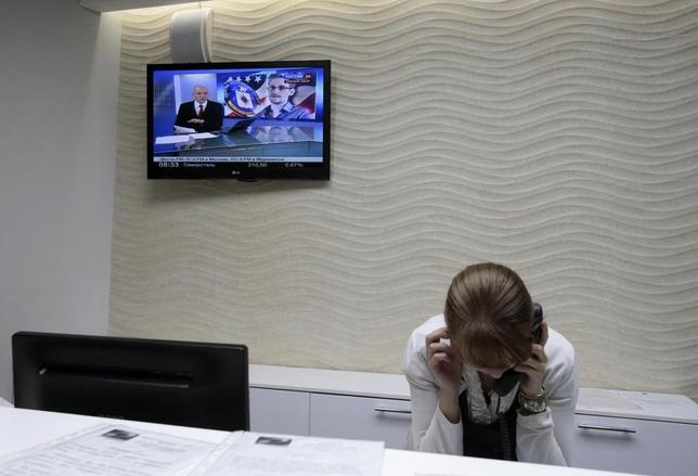 A receptionist talks on a phone while a picture of former U.S. NSA contractor Edward Snowden is shown on the television screen in the Capsule Hotel ''Air Express'' at the transit area of Moscow's Sheremetyevo airport in this June 26, 2013 file photo. The latest row between Beijing and Washington has brightened the outlook for Chinese software firms, which have already seen improved sales and share prices since U.S. spying revelations a year ago by Edward Snowden, a former U.S. National Security Agency (NSA) contractor.     REUTERS/Tatyana Makeyeva/Files