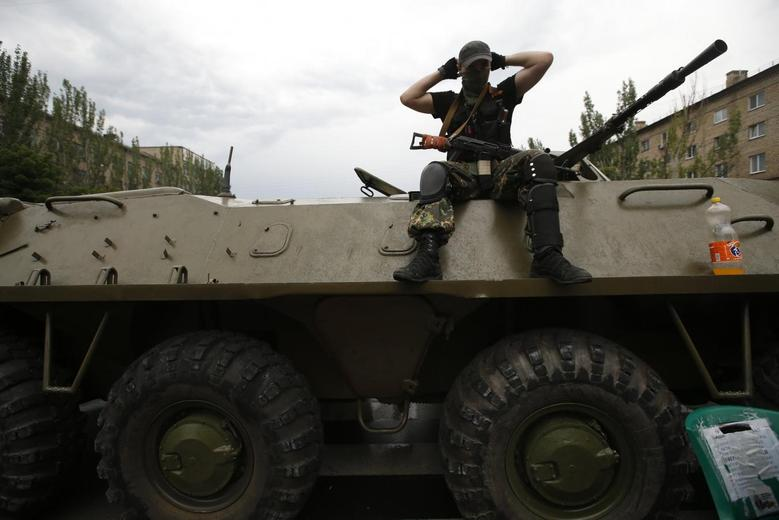 An armed pro-Russian separatist keeps watch from an armoured personnel carrier outside the regional administration building in the east Ukrainian city of Donetsk May 29, 2014. REUTERS/Maxim Zmeyev