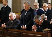 Poland's President Bronislaw Komorowski (R) and former Polish presidents Lech Walesa (L) kneel as Aleksander Kwasniewski (C) stands during a mass ceremony before the funeral of the last Communist leader general Wojciech Jaruzelski at a church in Warsaw May 30, 2014. REUTERS/Kacper Pempel