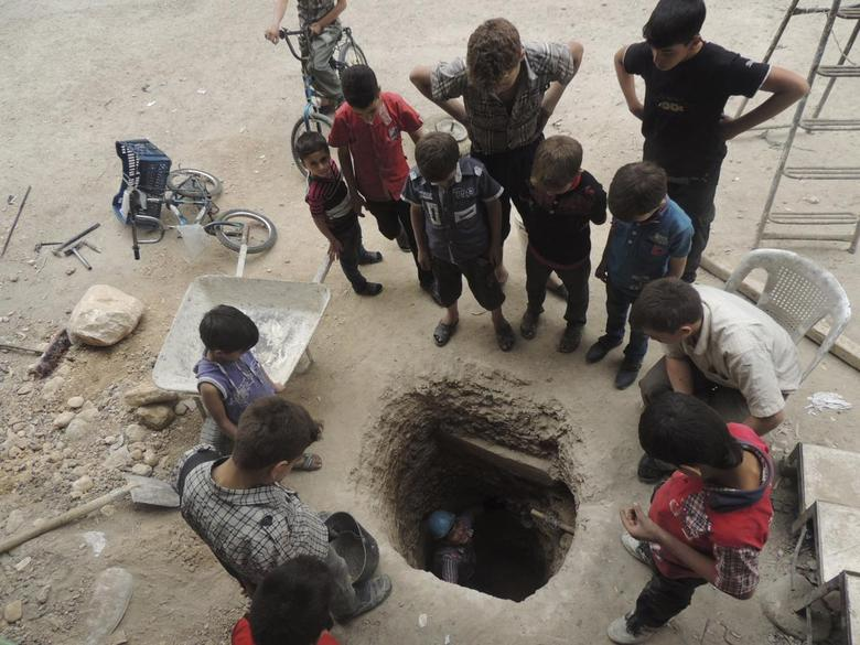 A boy looks up at his friends while digging a well in Arbeen, in the eastern Damascus suburb of Ghouta, May 6, 2014. REUTERS/Diaa Al-Din