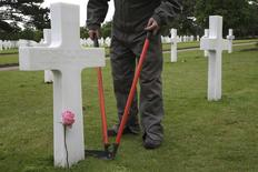 A gardener trims the grass near a tombstone in the American War cemetery ahead of Memorial Day ceremonies in Colleville-sur-Mer, in this May 23, 2014 file picture.REUTERS/Pascal Rossignol/Files