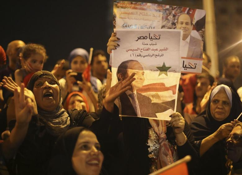 Supporters of Abdel Fattah al-Sisi hold a poster of him as they celebrate at Tahrir square in Cairo May 28, 2014.  REUTERS/Mohamed Abd El Ghany