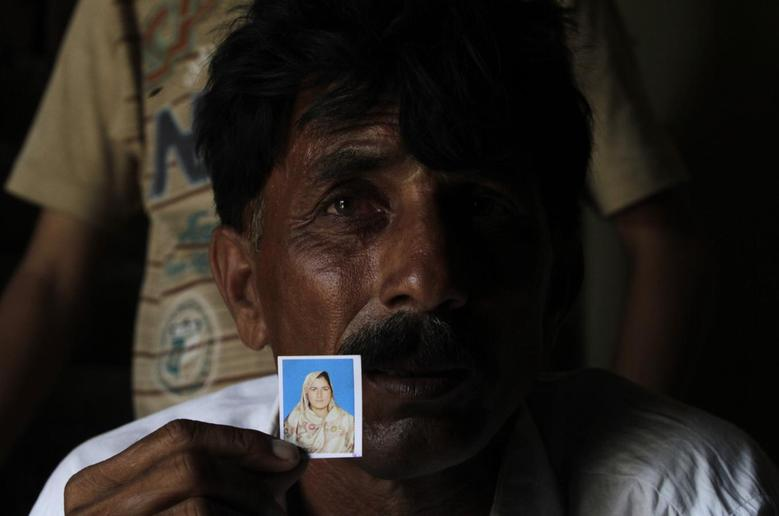 Muhammed Iqbal, 45, shows a picture of his late wife Farzana Iqbal, at his residence in a village in Moza Sial, west of Lahore May 30, 2014.  REUTERS/Mohsin Raza