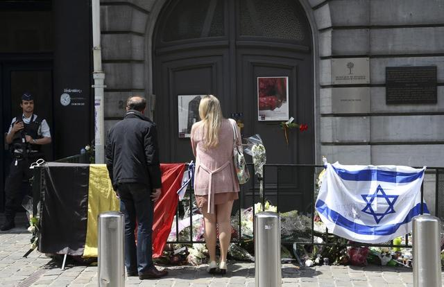 A couple stand in front of the Jewish Museum near a police officer in Brussels June 1, 2014.  REUTERS/Francois Lenoir