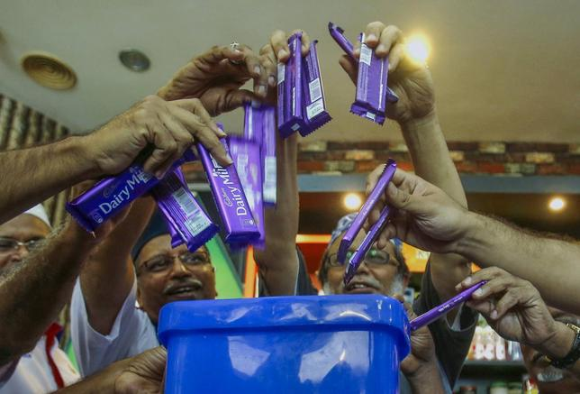 Members of Malaysian Muslim Wholesalers and Retailers Association (MAWAR), a non-governmental organization, throw Cadbury chocolate products into a dustbin as a protest and officially announced their boycott of Cadbury products, after their news conference on stopping the supply of Cadbury chocolate products to retail shops, in Kuala Lumpur May 29, 2014. REUTERS/Samsul Said