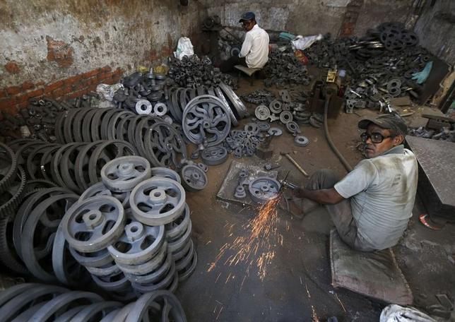 Workers grind iron bearings used in textile machinery inside a factory on the outskirts of Ahmedabad May 12, 2014. REUTERS/Amit Dave/Files