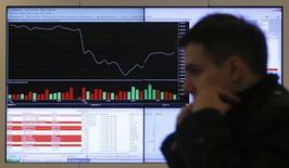 Мужчина проходит мимо экрана с рыночными котировками и графиками на Московской бирже, 14 марта 2014 года. Российский фондовый рынок продолжает рост в начале нового месяца при поддержке практически всех индексных акций, однако участники торгов не наблюдают энтузиазма у среднесрочных и долгосрочных инвесторов. REUTERS/Maxim Shemetov