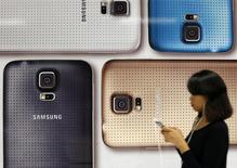 Девушка проходит мимо рекламы телефона Samsung Galaxy в Сингапуре 23 мая 2014 года. Корейская Samsung Electronics Co Ltd планирует выпустить первый смартфон на базе новой операционной системы Tizen в третьем квартале 2014 года, что должно помочь компании ослабить зависимость от ОС Android, продвигаемой Google Inc. REUTERS/Edgar Su