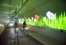 People cycle as they visit the 2nd Croix Rousse tunnel reserved for pedestrians, bicycles and buses in the night December 5, 2013. REUTERS/Robert Pratta