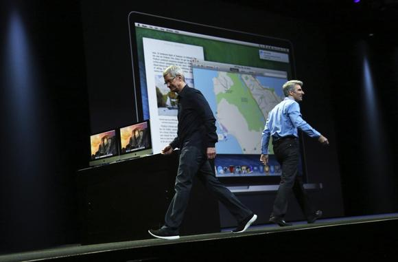 Apple CEO Tim Cook (L) walks off stage next to Apple vice president of software engineering  Craig Federighi, who introduced the new IOS X Yosemite operating system,  at the World Wide developers conference in San Francisco, California June 2, 2014. REUTERS/Robert Galbraith