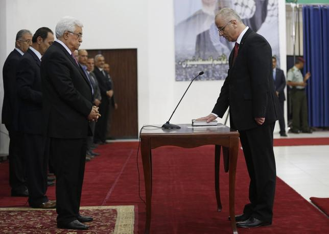 Palestinian Prime Minister Rami Hamdallah (R) stands in front of Palestinian President Mahmoud Abbas during a swearing-in ceremony of the unity government, in the West Bank city of Ramallah June 2, 2014. REUTERS/Mohamad Torokman