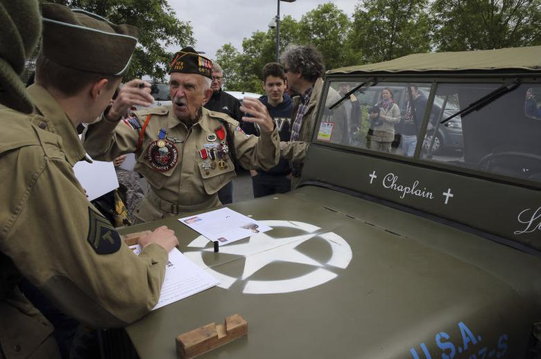 U.S. World War II veteran Jack W. Schlegel (2ndL), 91 years-old, from Mount Tremper, New York, of the 508th Parachute Infantry Division of the 82nd Airborne who parachuted near Sainte-Mere-Eglise on June 6,1944, gestures as he speaks about his D-Day experience to history enthusiasts as he visits the American War cemetery in Colleville-sur-Mer, on the Normandy coast June 2, 2014. REUTERS/Pascal Rossignol