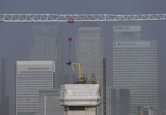 Builders work on a new building being constructed in the foreground of the Canary Wharf financial district, seen from the O2 Arena on a foggy morning in East London March 30, 2014. REUTERS/Andrew Winning