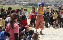 """Член организации """"Клоуны без границ"""" выступает перед сирийскими детьми в Джуб-Дженине, Ливан 2 июня 2014 года. Должны ли работники в сфере гуманитарной помощи всегда быть серьезными? Должны ли вы быть врачом, работающим на линии фронта, или волонтером, доставляющим еду беженцам? Дэвид Клэй, клоун из Орегона, так не думает. REUTERS/Sharif Karim"""