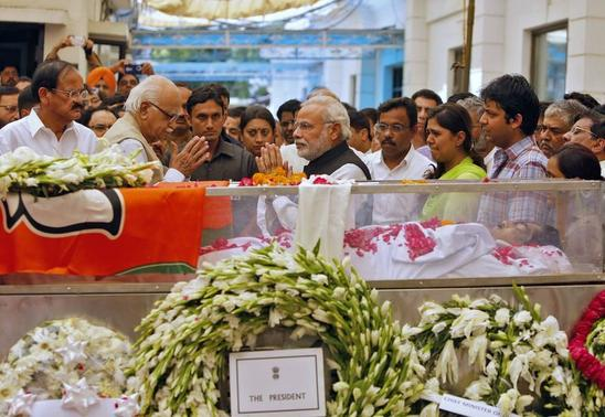 Prime Minister Narendra Modi (C) greets L.K. Advani, senior leader of  Bharatiya Janata Party (BJP), next to the casket of Rural Development Minister Gopinath Munde at the party headquarters in New Delhi June 3, 2014. REUTERS/Anindito Mukherjee