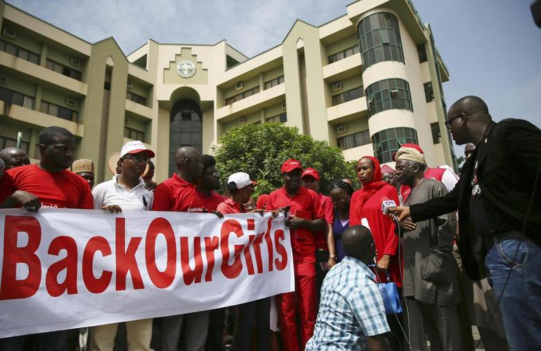 Members of the #BringBackOurGirls campaign group hold a banner next to their legal counsel Femi Falana (front 2nd L) outside Nigeria's National Human Rights Commission office after the group challenged the Nigerian police's ban on their daily protests, in Abuja June 3, 2014. REUTERS/Afolabi Sotunde