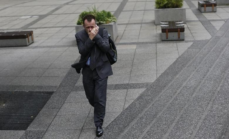A pedestrian shields his mobile phone from the wind as he walks through the City of London September 19, 2013.  REUTERS/Suzanne Plunkett