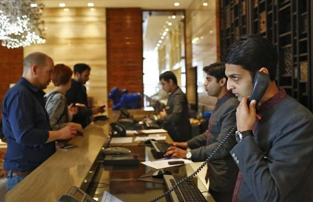 Receptionists attend to guests at their counter inside the Crown Plaza hotel, run by the InterContinental Hotels Group (IHG), in New Delhi January 31, 2014. REUTERS/Anindito Mukherjee/Files
