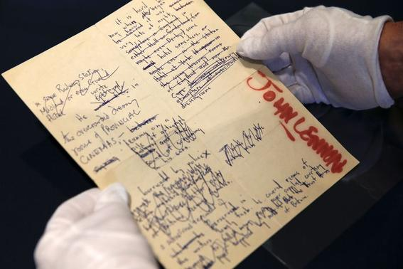 A Sotheby's employee handles a typescript signed by John Lennon during the press preview of a collection of Lennon's original drawings and manuscripts from 1964-65 at Sotheby's in New York May 29, 2014. REUTERS-Shannon Stapleton