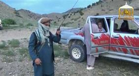 A Taliban militant speaks to U.S. Army Sergeant Bowe Bergdahl (R) waiting in a pick-up truck before his release at the Afghan border, in this still image from video released June 4, 2014.   REUTERS/Al-Emara via Reuters TV