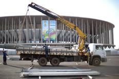 Men load metallic structures into a vehicle outside the Mane Garrincha National Stadium, one of the venues for the upcoming 2014 World Cup, in Brasilia in this May 31, 2014 file photo.  REUTERS/Ueslei Marcelino/Files