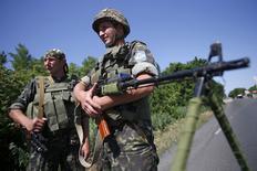 Soldats ukrainiens à un barrage routier dans la région de Donetsk, dans l'est de l'Ukraine. La Banque centrale européenne (BCE) a fait part jeudi de son inquiétude croissante face à une possible escalade des tensions entre l'Ukraine et la Russie de nature à affecter la zone euro via les relations commerciales et financières avec Moscou et le prix du pétrole. /Photo prise le 5 juin 2014/   REUTERS/Maxim Zmeyev