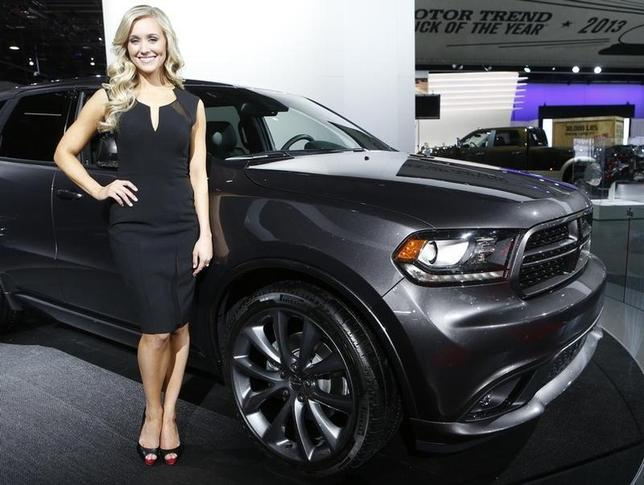 Model Erin Wolak poses next to a 2014 Dodge Durango during the press preview day of the North American International Auto Show in Detroit, Michigan January 14, 2014.  REUTERS/Rebecca Cook