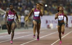 Jamaica's Shelly-Ann Fraser-Pryce (R) runs next to her compatriot Kerron Stewart (L) and Blessing Okagbare of Nigeria during the women's 100m event at the IAAF Diamond League athletics meet, in Doha May 9, 2014. REUTERS/Fadi Al-Assaad