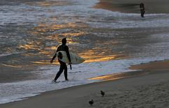 A surfer walks along Ipanema Beach in Rio de Janeiro June 4, 2014.  REUTERS/Sergio Moraes