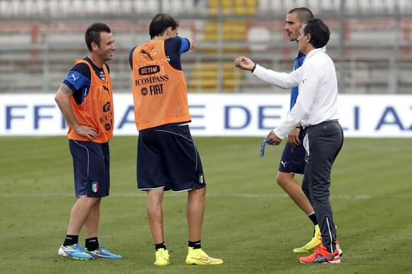Italy's national soccer team coach Cesare Prandelli (R) talks to his players Antonio Cassano (L), Gabriel Paletta (2nd L) and Leonardo Bonucci during a training session at Renato Curi stadium in Perugia June 3, 2014.  REUTERS/Giampiero Sposito