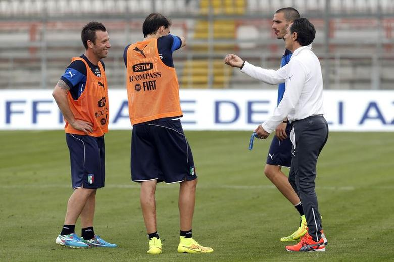 Italy's national soccer team coach Cesare Prandelli (R) talks to his players Antonio Cassano (L), Gabriel Paletta (2nd L) and Leonardo Bonucci during a training session at Renato Curi stadium in Perugia June 3, 2014.  REUTERS/Giampiero Sposito