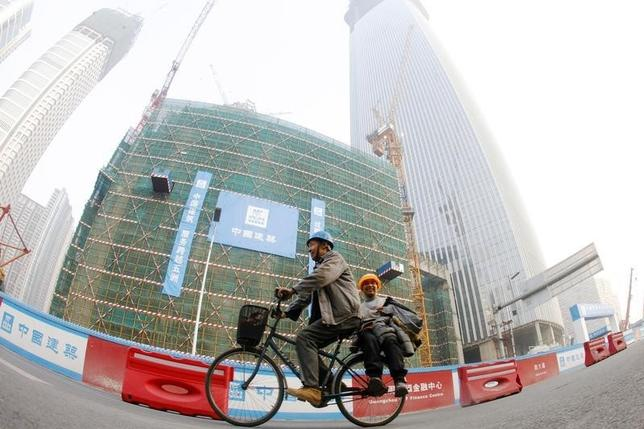 Workers ride a bicycle past a financial building construction site in the central business district in Guangzhou, Guangdong province February 17, 2014. REUTERS/Alex Lee