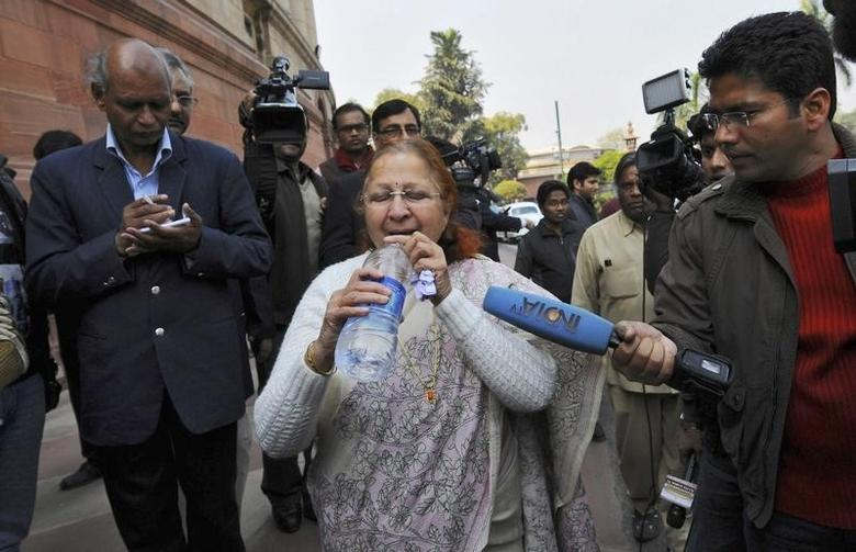 Sumitra Mahajan drinks water after she rushed out of the parliament in New Delhi February 13, 2014. REUTERS/Adnan Abidi/Files