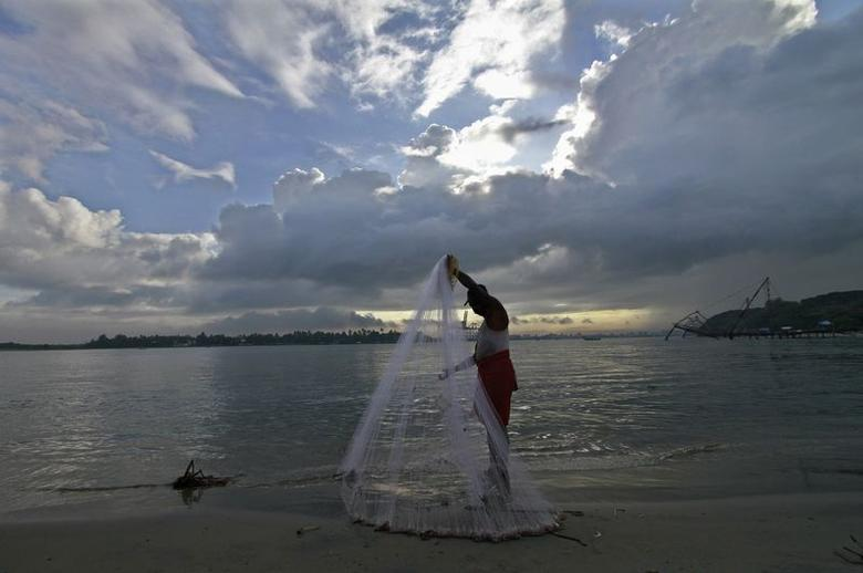A fisherman arranges his fishing net at a beach against the backdrop of pre-monsoon clouds in the southern Indian city of Kochi June 5, 2014. REUTERS/Sivaram V.