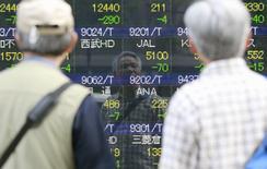 Прохожие у брокерской конторы в Токио, 16 мая 2014 года. Азиатские фондовые рынки завершили неделю разнонаправленно под влиянием локальных факторов. REUTERS/Yuya Shino