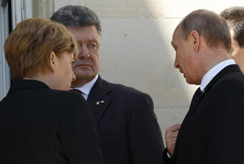 Ukraine president-elect Petro Poroshenko (2nd L), German Chancellor Angela Merkel (L) and Russian President Vladimir Putin talk after a group photo during the 70th anniversary of the D-Day landings in Benouville, France June 6, 2014. REUTERS/Kevin Lamarque