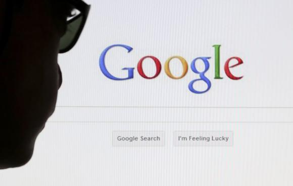 A computer user poses in front of a Google search page in this photo illustration taken in Brussels May 30, 2014. REUTERS/Francois Lenoir