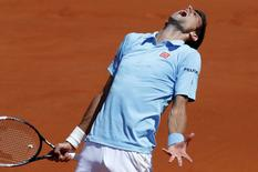 Novak Djokovic of Serbia reacts during his men's semi-final match against Ernests Gulbis of Latvia at the French Open tennis tournament at the Roland Garros stadium in Paris June 6, 2014. REUTERS/Jean-Paul Pelissier