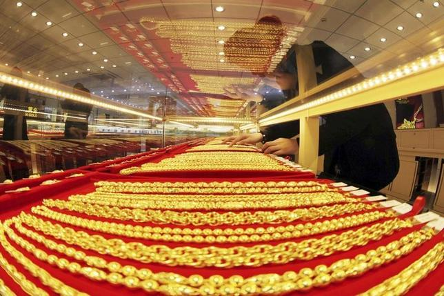 A sales assistant arranges gold necklaces at a store in Lianyungang, Jiangsu province, January 23, 2014. REUTERS/China Daily/Files