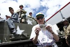 A veteran shows a picture of his unit as he attends a ceremony to commemorate the 70th anniversary of the D-Day landings, in Old Bethpage, New York, June 6, 2014. REUTERS/Eduardo Munoz