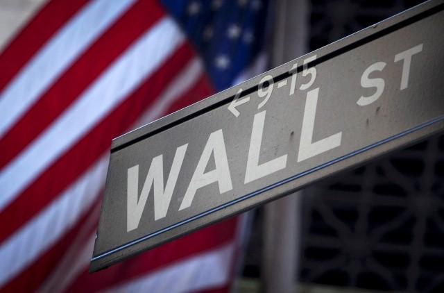 A Wall Street sign is pictured outside the New York Stock Exchange in New York, October 28, 2013.  REUTERS/Carlo Allegri/Files
