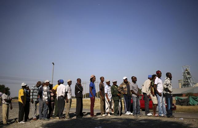 Members of the mining community wait for food parcels donated by an Aid organisation, Gift of the Givers, at the Khomanani mine in Rustenburg May 28, 2014.  REUTERS/Siphiwe Sibeko