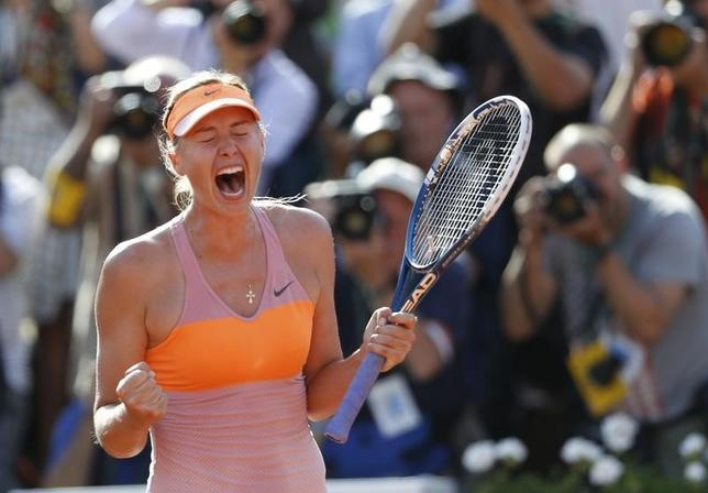 Maria Sharapova of Russia celebrates after winning her women's singles final match against Simona Halep of Romania at the French Open tennis tournament at the Roland Garros stadium in Paris June 7, 2014. REUTERS/Vincent Kessler