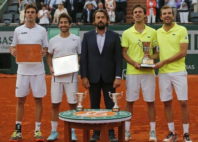 Julien Benneteau (R) and Edouard Roger-Vasselin (2ndR) of France pose with the trophy and former French tennis player Henri Leconte (C) during the ceremony after winning their men's doubles final match against Marcel Granollers (L) and Marc Lopez (2ndL) of Spain at the French Open Tennis tournament at the Roland Garros stadium in Paris June 7, 2014. REUTERS/Jean-Paul Pelissier