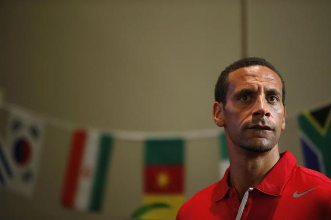 Former Manchester United player Rio Ferdinand looks on in front of flags of nations participating in the World Cup during a promotional event where he and Manchester City's Sergio Aguero compete for the most popular ''selfie'' in Singapore May 15, 2014. REUTERS/Edgar Su