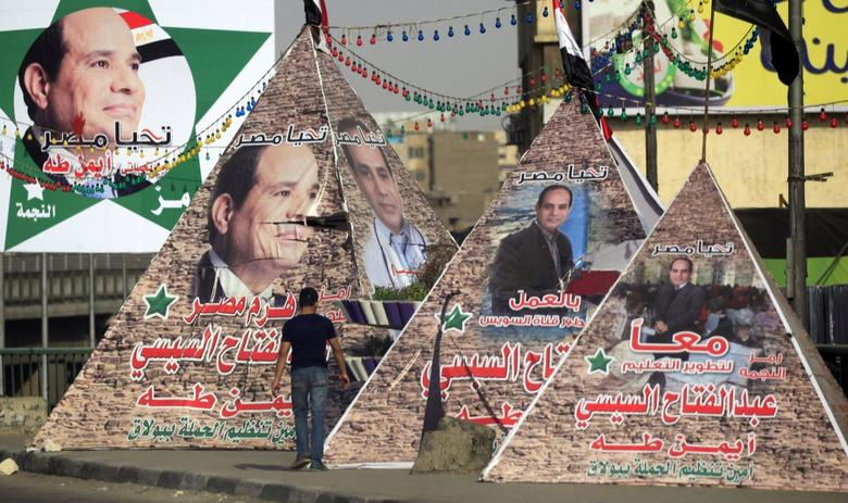 A man walks near replicas of Giza Pyramid covered with banners of presidential candidate and former army chief Abdel Fattah al-Sisi in Cairo May 26, 2014.  REUTERS/Amr Abdallah Dalsh