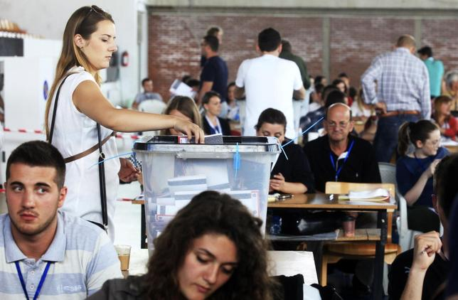 A Kosovo Albanian woman places her ballot paper into a voting box at the polling station in the capital city Pristina June 8, 2014. REUTERS/Hazir Reka