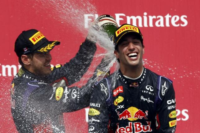 Third place finisher Red Bull Formula One driver Sebastian Vettel of Germany (L) sprays teammate and winner Red Bull Formula One driver Daniel Ricciardo of Australia after the Canadian F1 Grand Prix at the Circuit Gilles Villeneuve in Montreal June 8, 2014. REUTERS/Chris Wattie