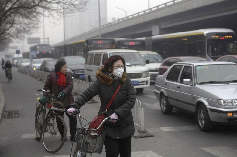 A woman (C) wearing a mask stands besides her bicycle as vehicles stop at a traffic junction on a busy street amid thick haze in Beijing in this February 25, 2014 file photo. REUTERS/Barry Huang/Files