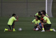 Neymar tira foto de menino que invadiu treino da seleção com jogadores da equipe. 08/06/2014  REUTERS/Marcelo Regua